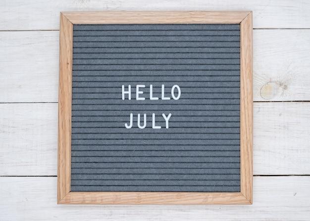 Texte anglais bonjour juillet sur un tableau de lettres en lettres blanches