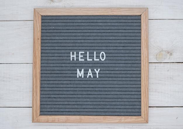 Texte anglais bonjour mai sur un tableau de lettres en lettres blanches