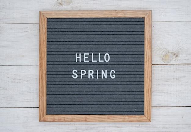 Texte anglais bonjour printemps sur un tableau de lettres en lettres blanches