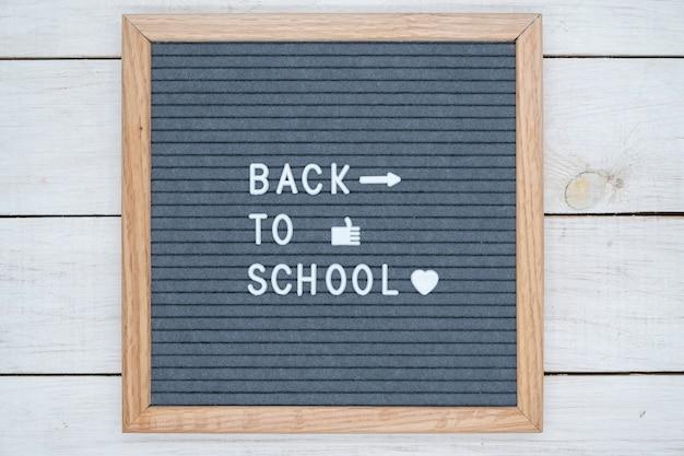 Texte anglais de retour à l'école sur un panneau de feutre gris en lettres blanches et symboles comme, coeur et flèche