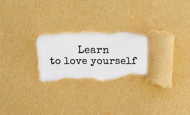 Texte apprenez à vous aimer apparaissant derrière du papier brun déchiré