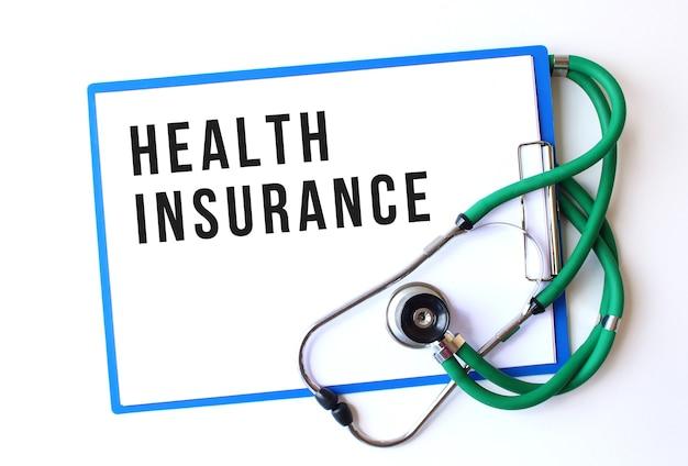 Texte d'assurance maladie sur dossier médical avec documents et stéthoscope sur fond blanc. concept médical.