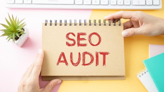 Texte d'audit seo sur le papier jaune avec téléphone, café, stylo