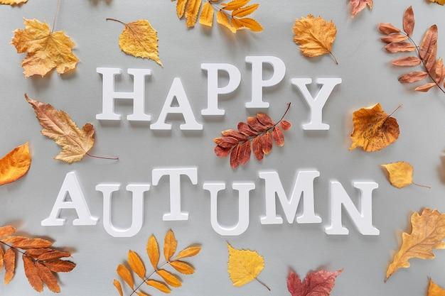 Texte d'automne heureux de lettres blanches et de feuilles colorées sur fond gris. concept de vacances d'automne. vue de dessus mise à plat