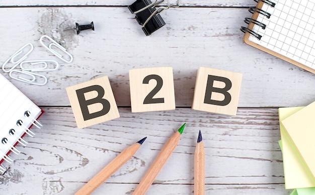 Texte b2b sur bloc de bois avec des outils de bureau sur le fond en bois