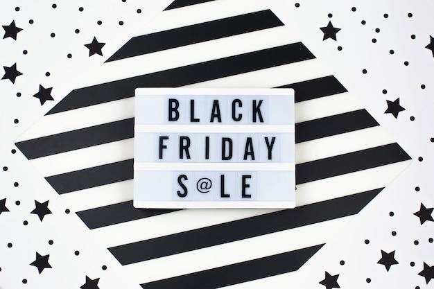 Texte de bannière de vente vendredi noir sur lightbox blanc et étoiles noires autour