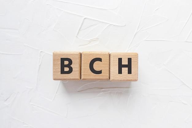 Texte bch sur cubes en bois sur fond bleu fourchette de crypto-monnaie bitcoin cash de bitcoin square wo