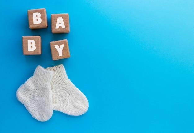 Texte de bébé sur des cubes de bois et paire de chaussettes tricotées mignonnes sur bleu