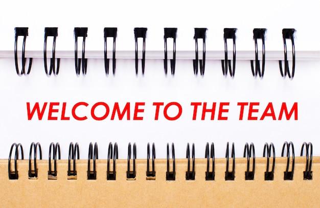Texte bienvenue à l'équipe sur du papier blanc entre les blocs-notes à spirale blanc et marron.
