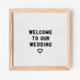 Texte de bienvenue pour mariage sur cadre en bois avec toile de fond blanche