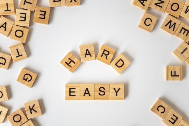 Texte de bloc de lettre en bois dur et facile avec d'autres lettres sur fond blanc.