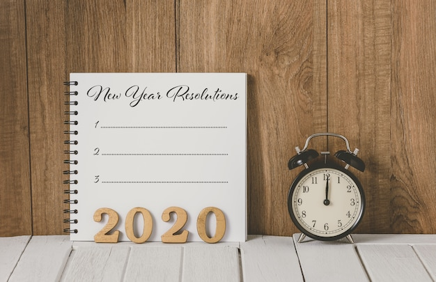 Texte en bois 2020 et liste de résolutions du nouvel an rédigés sur un cahier avec réveil