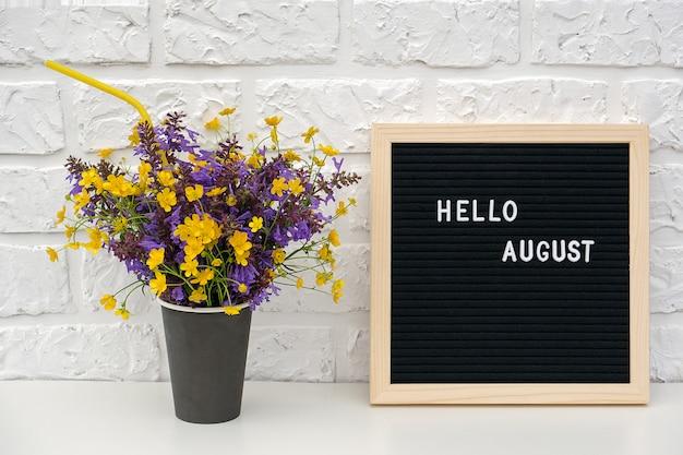 Texte bonjour août sur le tableau de lettres noir et bouquet de fleurs colorées dans une tasse de café en papier noir