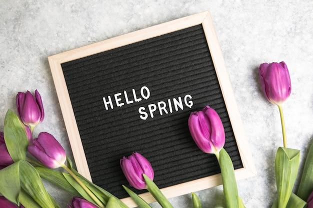 Texte bonjour printemps sur carton à lettres et bouquet de fleurs de tulipes violettes