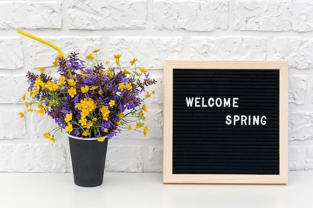 Texte bonjour printemps sur tableau noir et bouquet de fleurs colorées dans une tasse à café en papier noir avec paille cocktail