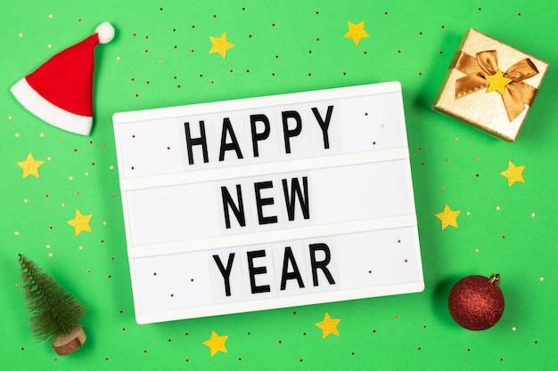 Texte de bonne année dans une boîte à lumière, décorations et paillettes sur fond vert