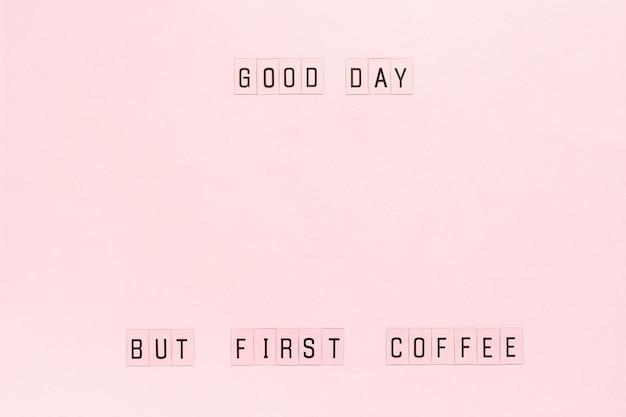 Texte bonne journée, mais premier café sur un fond de papier rose pastel.