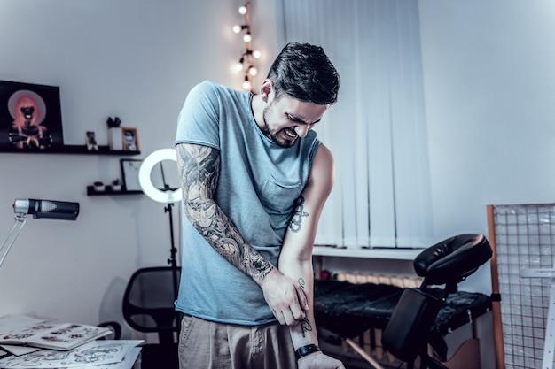 Texte bourré. homme aux cheveux noirs confus, grattant agressivement son tatouage primitif sur le côté intérieur de la main