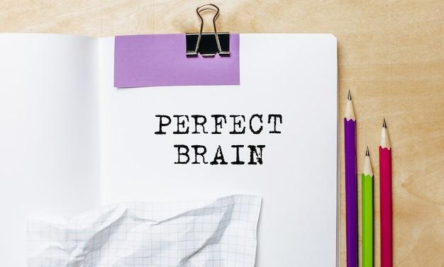 Texte de cerveau parfait écrit sur un papier avec des crayons sur le bureau au bureau