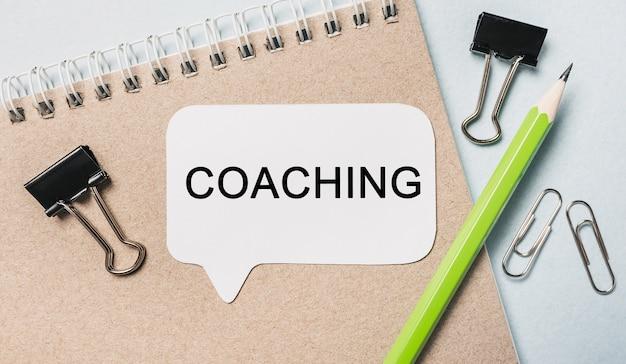 Texte coaching sur un autocollant blanc avec fond de papeterie de bureau. mise à plat sur le concept d'entreprise, de finance et de développement