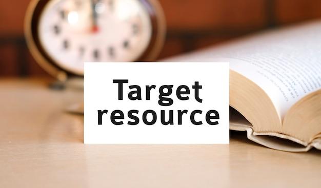 Texte de concept d'entreprise de ressource cible sur un livre blanc et une horloge