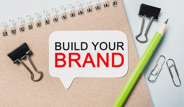 Texte construisez votre marque sur un autocollant blanc avec des articles de papeterie de bureau