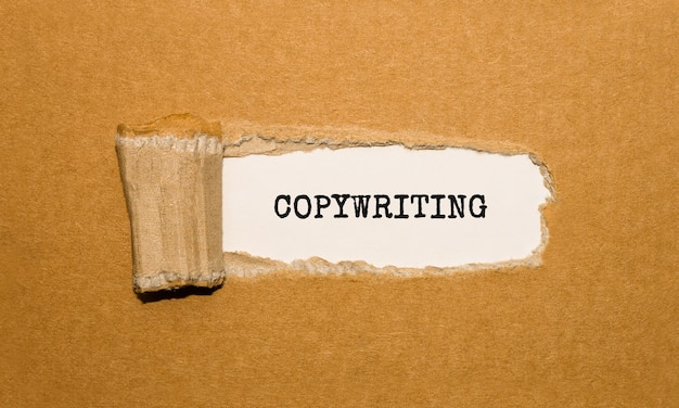 Le texte copywriting apparaissant derrière du papier brun déchiré