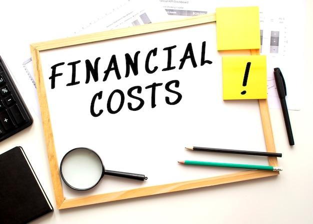 Le texte des cots financiers est écrit sur un tableau de bureau blanc sur le bureau