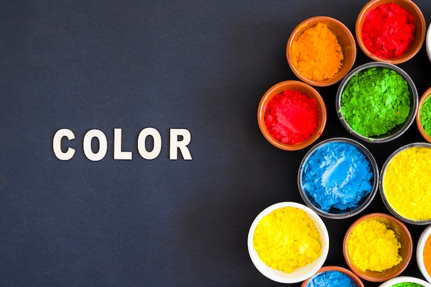 Texte en couleur avec différents types de poudre de couleur holi dans le bol sur fond noir
