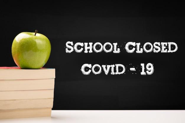 Texte covid-19 fermé à l'école écrit sur tableau noir en gros plan