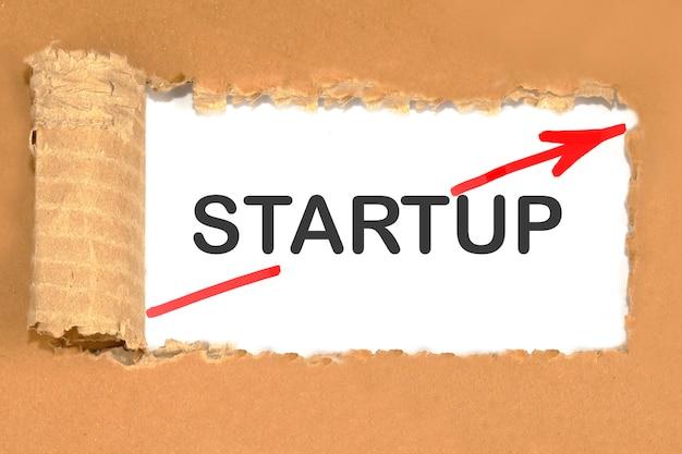 Texte de démarrage sur un carton déchiré avec une flèche rouge indiquant un démarrage rapide à partir de zéro.