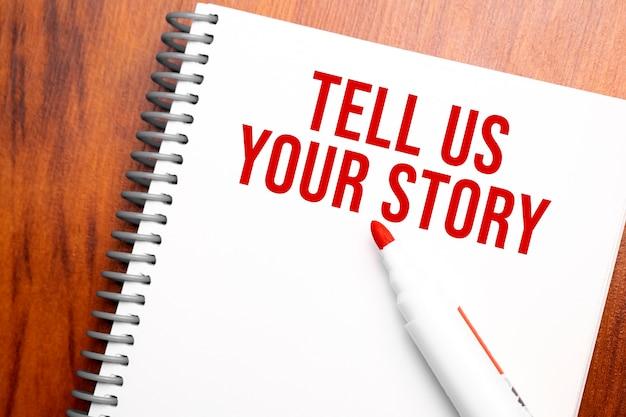 Texte dites-nous votre histoire écrit dans le bloc-notes, table en bois de bureau d'en haut, image conceptuelle pour le titre du blog ou l'image d'en-tête. aspect de couleur vintage vieilli.