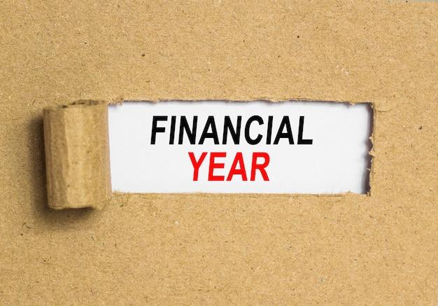 Le texte «économisez aujourd'hui pour demain». derrière du papier brun déchiré. image de concept d'entreprise. année financière