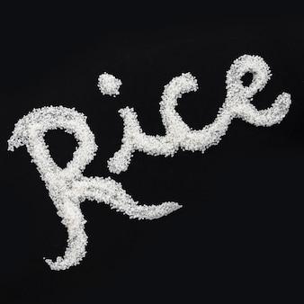 Texte écrit avec du riz non cuit sur fond noir