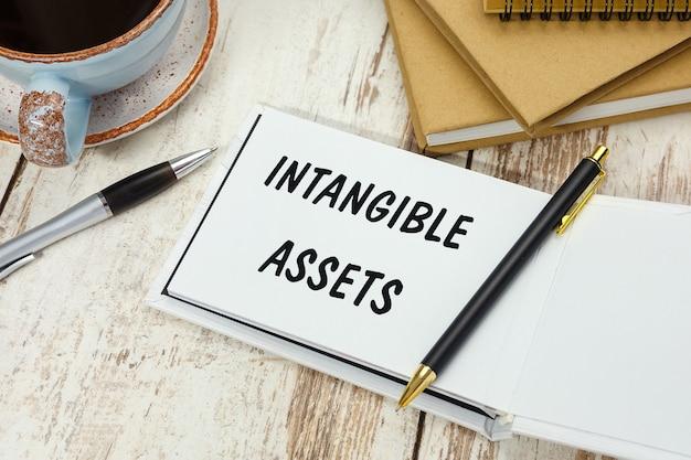 Texte de l'écriture des actifs incorporels sur le bloc-notes sur l'arrière-plan du bureau