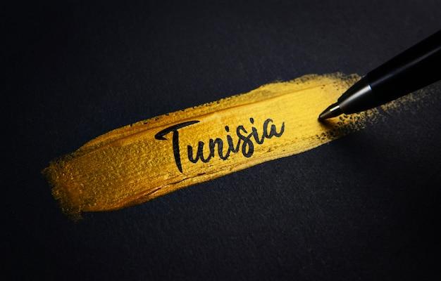 Texte d'écriture de la tunisie sur le coup de pinceau de peinture d'or
