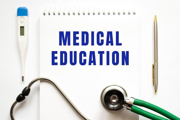 Texte de l'éducation médicale écrit dans un cahier posé sur un bureau et un stéthoscope