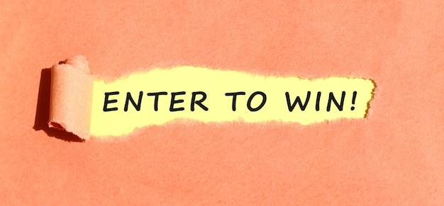 Le texte entrer pour gagner apparaissant sur du papier jaune derrière du papier couleur déchiré vue de dessus