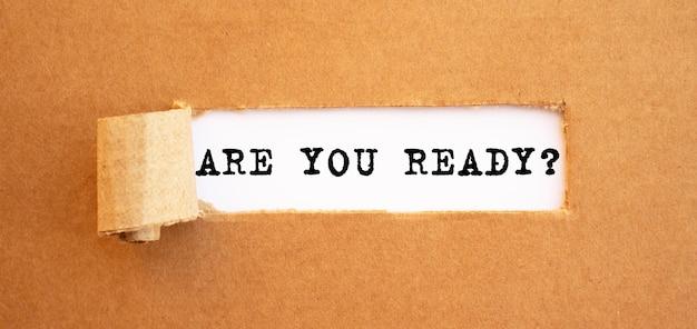 Le texte êtes-vous prêt apparaissant derrière du papier brun déchiré.