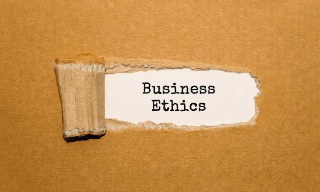 Le texte de l'éthique des affaires apparaissant derrière du papier brun déchiré