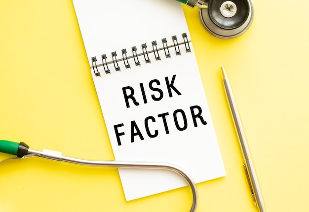 Texte facteur de risque sur ordinateur portable avec stéthoscope et stylo