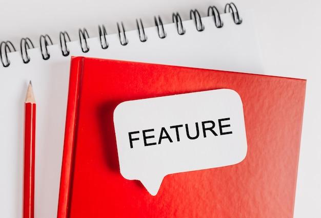 Texte feature sur un autocollant blanc sur un bloc-notes rouge avec fond de papeterie de bureau. mise à plat sur le concept d'entreprise, de finance et de développement