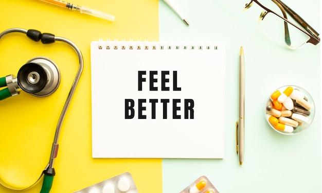 Texte feel better sur ordinateur portable avec stéthoscope et stylo sur une surface jaune.
