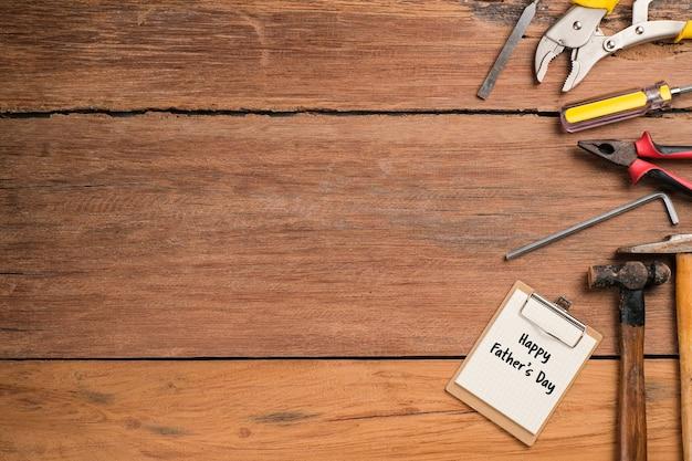 Texte de la fête des pères heureux avec bordure latérale d'outils et de cravates sur fond de bois rustique
