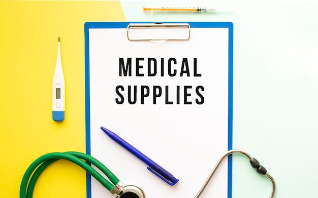 Texte de fournitures médicales sur un en-tête dans un dossier médical sur un beau fond. stéthoscope, thermomètre et stylo.