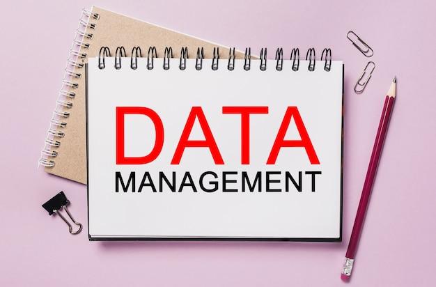 Texte gestion des données sur un bloc-notes blanc avec fond de papeterie de bureau. mise à plat sur le concept d'entreprise, de finance et de développement