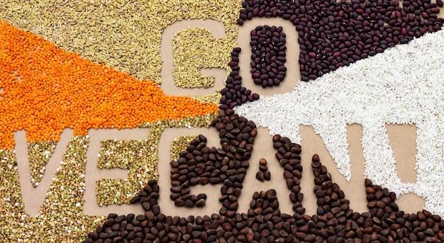 Texte go vegan bordé de diverses céréales et noix sur un fond de papier kraft. lettrage de nourriture.