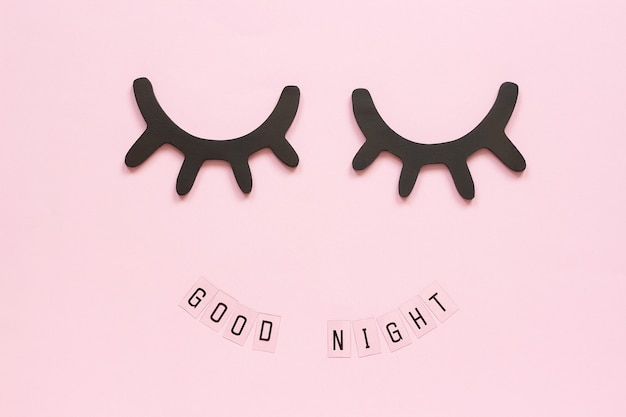 Texte good night et cils noirs en bois décoratifs, yeux fermés sur fond rose