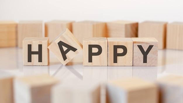 Texte heureux sur des blocs en bois, fond gris