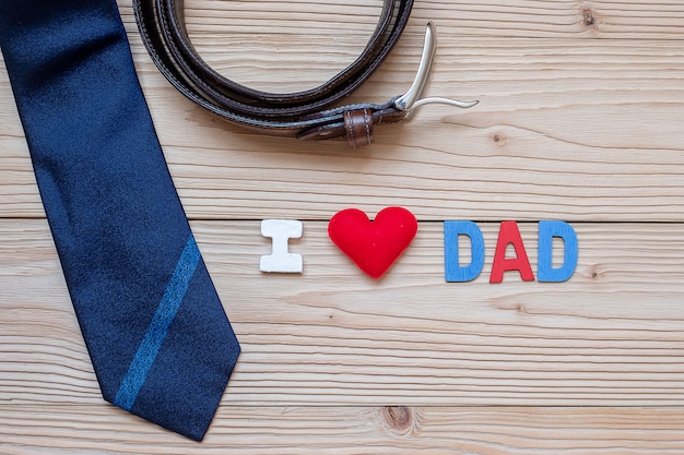 Texte i love dad avec des cravates bleues, une ceinture et une forme de coeur rouge sur bois